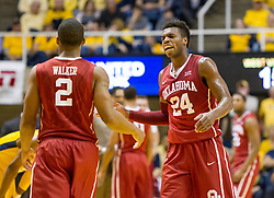 Feb 20, 2016; Morgantown, WV, USA; Oklahoma Sooners guard Buddy Hield (24) talks with guard Dinjiyl Walker (2) during the first half against the West Virginia Mountaineers at the WVU Coliseum. Mandatory Credit: Ben Queen-USA TODAY Sports