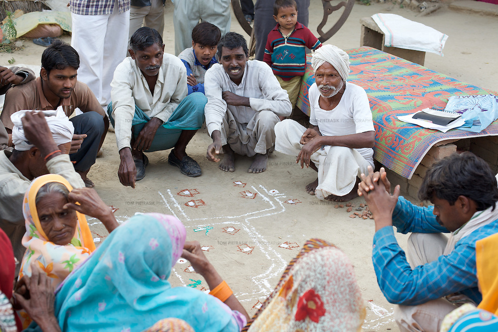 Residents from Khanjadipur village undertake a community mapping (Participatory Rapid Appraisal or PRA) exercise with government consultant and district project coordinator, Vinod Srivastava (not in photo). Community mapping illustrates the distribution of water and sanitation facilities in a village and provides an opportunity for residents to propose solutions to any shortcomings the mapping exposes. ..UNICEF and the Uttar Pradesh Government, have identified 36 model Gram Panchayats (local-level village administration) in Mirzapur District. The promotion of good sanitation and hygiene practices in these Gram Panchayats allows them to serve as examples for the remaining areas of the district to emulate. The promotion of hygiene and sanitation includes the construction and painting of school toilet blocks, the construction of individual toilets in households, the digging of garbage pits, recycling waste water and encouraging personal hygiene awareness. ..Only 32 percent of those living in Uttar Pradesh, India's largest state, have access to a toilet. Uttar Pradesh faces many challenges in it's efforts to address this deficiency. UNICEF supports the Uttar Pradesh government's sanitation and hygiene project at both the state and district levels. UNICEF is working to increase the capacity of all of those involved in the sanitation and hygiene project from state-level administrators through to Panchayati Raj (local-level administration) officers and influential individuals, including teachers, who live among rural communities. UNICEF has prioritised the need to communicate the importance of good sanitation and hygiene practice to these communities. The Uttar Pradesh government and UNICEF have focussed their campaign on eight districts (including Mirzapur) with the intention that these serve as models for the remaining 62 districts of the state. UNICEF have identified areas of shortcoming within the government program and proposed solutions. These solutions include the p