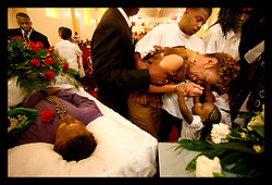 04 August 2006 - New Orleans - Louisiana. Funeral - New Home Baptist Church. Friends and relatives of three young men gunned down late at night on a city street on July 28th pay their respects. 4 men were gunned down that night in one incident as crime spirals out of control in New Orleans. Three of the victims, all brothers buried today are Kadeem Stephen (16yrs), Kendall Stephen (21yrs) and Kareem Stephen (also 16yrs). Pictured is the boy's aunt, Anita Mikell, overcome with grief as she is led to the open coffins. A young child reaches up to console her.