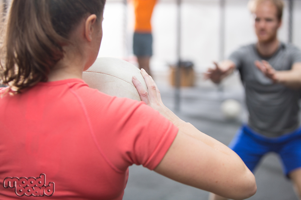 Rear view of woman throwing medicine ball towards man in crossfit gym