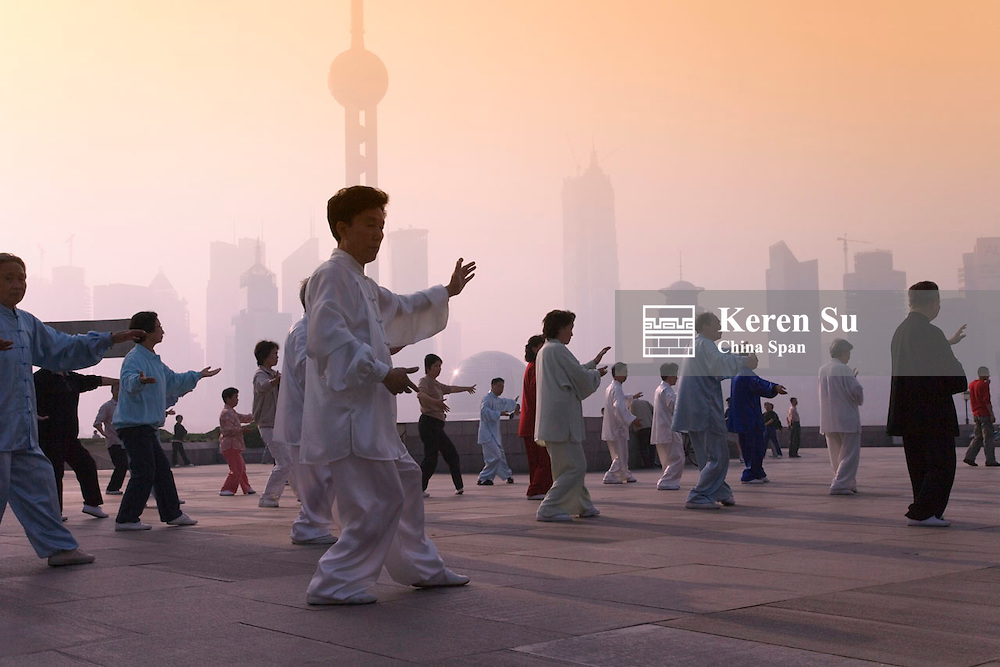 People doing Taiji on the Bund, Pudong skyline in the distance, Shanghai, China