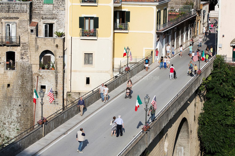 SANT'AGATA DE GOTI, ITALY - 23 JULY 2014: Locals walk on the bridge decorated with Italian and American flags to celebrate the arrival of Mayor of New York Bill de Blasio in Sant'Agata de Goti, his ancestral home town in Italy, on July 23rd 2014.<br /> <br /> New York City Mayor Bill de Blasio arrived in Italy with his family Sunday morning for an 8-day summer vacation that includes meetings with government officials and sightseeing in his ancestral homeland.