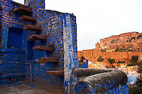 Blue painted house wall with Mehrangarh Fort in the distance, Jodhpur, Rajasthan, India. Exotic locations fine art photography prints for sale.