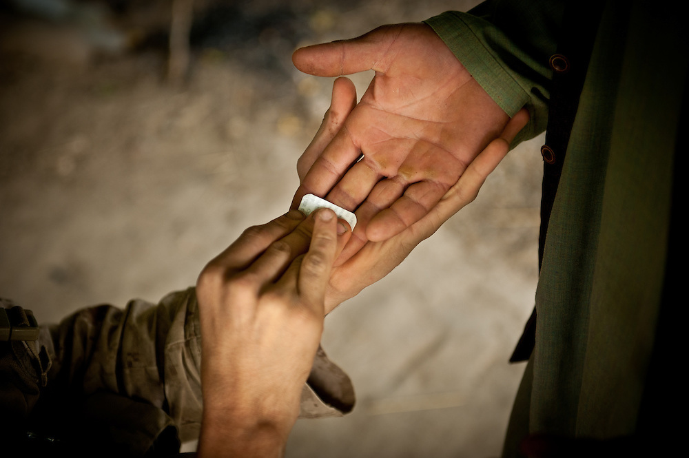 A Marines swipes an Afghan's hand with a special pad used to detect the presence of explosive materials.