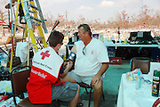 Waveand Mississippi Sept. 16, 2005, Brian Mollere gets his blood pressure checked by a American Red Cross Disaster Relief worker days after he survived swimming thru Hurricane Katrina with his dog Rocky. Rescue workers find him sitting on his concrete slab with his dog where their house used to be. Hurricane Katrina destroyed their home, the city of Waveland and Brian and Rocky were swept up in a 30ft wall of water and carrried over a half mile across the trian tracks. Brian had sent his mother to higher ground to ride out the storm but he decieded to stay and protect her home, the house was completely destroyed and his mother died in the storm ,she was in Bay St. Louis about 10 miles from her home. Brian was one of only a few eople who stayed in Waveland to ride the storm out and surrived to tell his story. ©SUZI ALTMAN PHOTOGRAPHER www.suzisnaps.com .cell phone 601-668-9611.