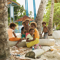 Papua kids playing on a sandy beach in the shade of coconut trees.