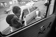 Two kids with toy gun outside camper van window.High Wycombe. UK, 1990.