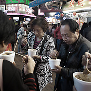 A group of Chinese Christmas shoppers eat street food in Time's Square, shotly before Christmas. <br />
