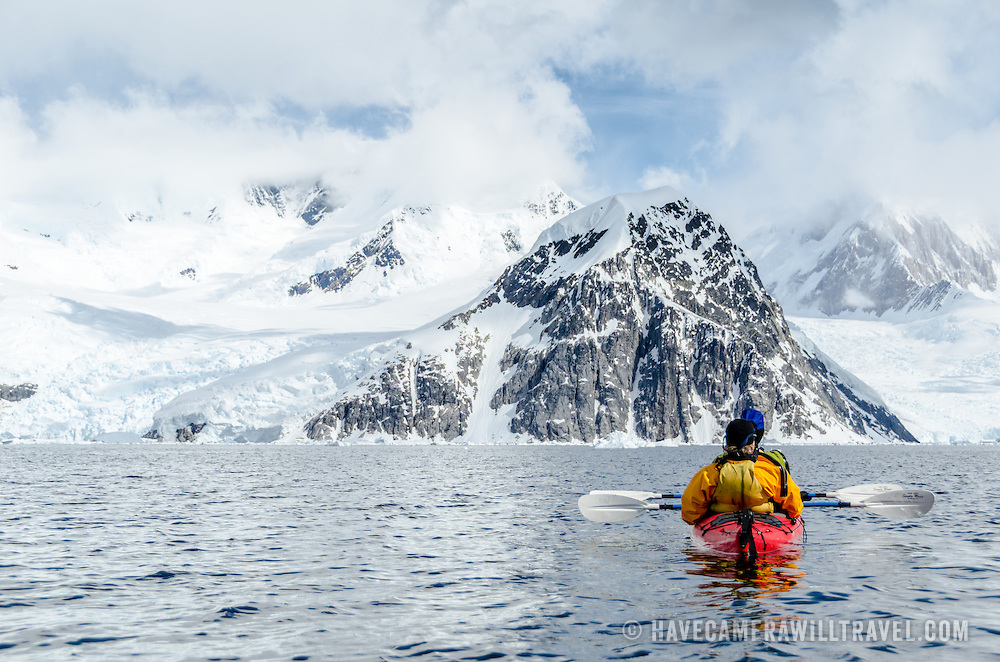 Kayakers in a tandem sea kayak head towards a steep rocky mountain at Neko Harbour, Antarctica.