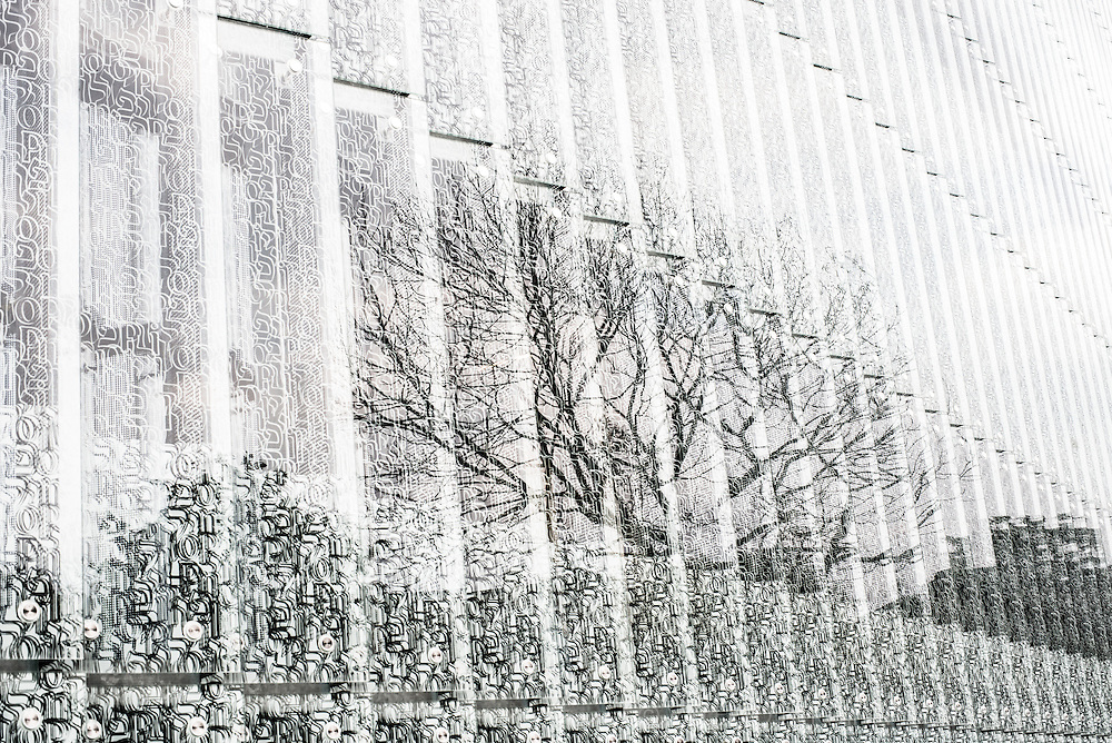 A tree reflects onto the facade of The Museum of History of Polish Jews. A postmodern structure in glass, copper, and concrete, designed by Finnish architects Rainer Mahlamäki and Ilmari Lahdelma, is located on the site of the former Warsaw Ghetto. The museum features a multimedia narrative exhibition about the vibrant Jewish community that flourished in Poland for a thousand years. Trees are considered silent witnesses of the inhuman Nazi cruelty. A bronze cast of a famous elm tree  standing in front of Pawiak prison was erected once the original tree died in 1983.