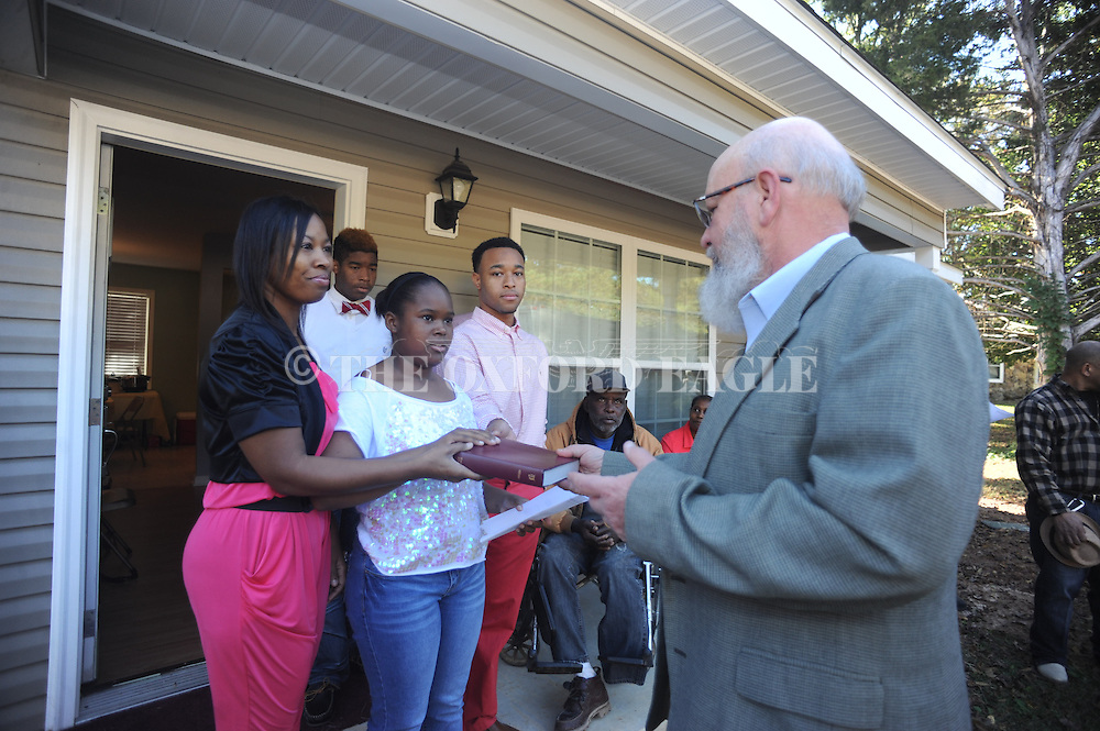 Darryail Whittington (right) presents a Bible as Habitat for Humanity dedicates a new house for Nakia Carrothers (left), Nayiah Dean (center), and Zell Pettis in Oxford, Miss. on Sunday, November 3, 2013.