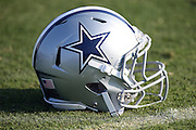 A Dallas Cowboys helmet lies on the grass during the second day of the Dallas Cowboys 2016 NFL training camp football practice held on Sunday, July 31, 2016 in Oxnard, Calif. (©Paul Anthony Spinelli)