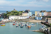 Pleasure boats - powerboats and yachts in harbour - seaside housing and town, Tenby, Wales, UK