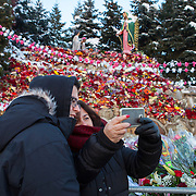 Taking time for a selfie with a smart phone during the Feast Our Lady of Guadalupe celebration annual two-day feast celebration of Mexico's patron saint. Braving extremely cold temperatures, believers from the Chicago area and other parts of the United States gather day and night to pay homage at the shrine.    Photography by Jose More