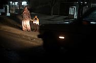 A young mother with her child is attempting to cross the road. Since the black-outs became more frequent the number of road incidents raised. Una giovane donna con un bambino tentano di attraversare la strada. Durante il black out il numero d'incidenti stradali e' molto aumentato.