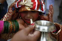 August 8, 2017 - Kathmandu, Nepal - A child drinks milk offered by a devotee as rituals during a procession to celebrate Gai Jatra or Cow Festival in Basantapur, Kathmandu, Nepal on Tuesday, August 8, 2017. People from the Newar community commemorate the festival to wish peace for their deceased family members from preceding years. (Credit Image: © Skanda Gautam via ZUMA Wire)