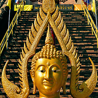 Golden Buddha with Halo at Wat Chedi Luang in Chiang Mai, Thailand <br /> This golden Buddha with an elliptical halo sits below a parasol at the base of the ancient pagoda at Wat Chedi Luang. Its design is from the 14th century Sukhothai period.  In the background you can see part of the southern staircase that leads up to the first platform.  Although the brick chedi is much shorter than it was when it was finished during the 15th century, it still stands at an impressive 269 feet.