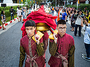 18 NOVEMBER 2015 - BANGKOK, THAILAND:  People carry the red cloth that will be placed around the chedi at Wat Saket during the parade marking the start of the temple's annual fair. Wat Saket is on a man-made hill in the historic section of Bangkok. The temple has golden spire that is 260 feet high which was the highest point in Bangkok for more than 100 years. The temple construction began in the 1800s in the reign of King Rama III and was completed in the reign of King Rama IV. The annual temple fair is held on the 12th lunar month, for nine days around the November full moon. During the fair a red cloth (reminiscent of a monk's robe) is placed around the Golden Mount while the temple grounds hosts Thai traditional theatre, food stalls and traditional shows.     PHOTO BY JACK KURTZ