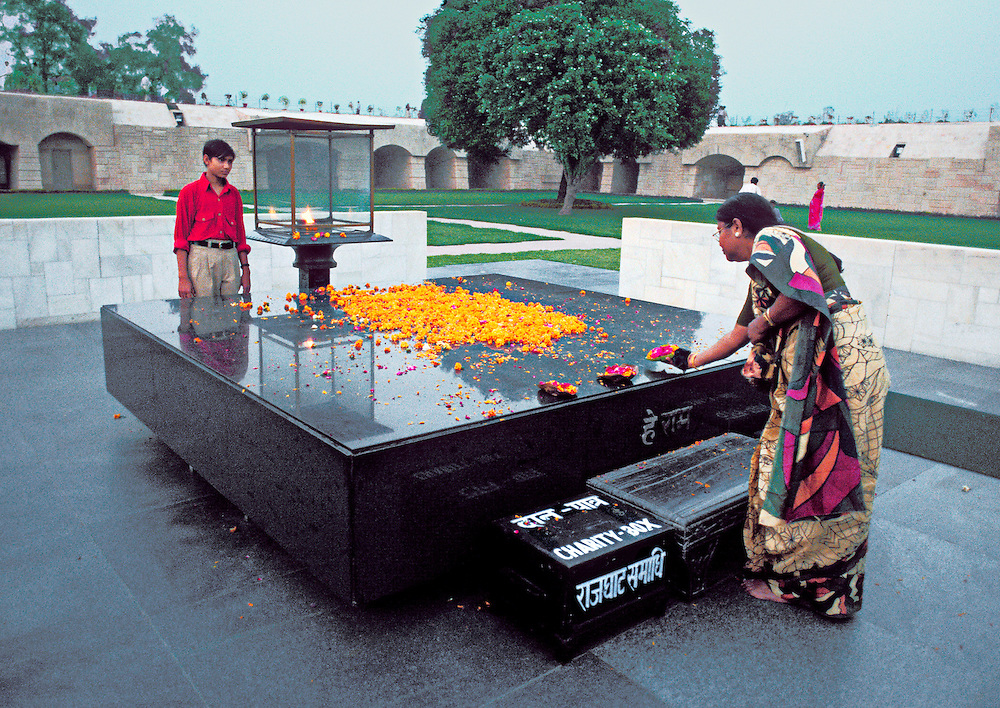 "Rajghat, Delhi, memorial with eternal flame and ""charity box"" at the site of the Ghat where Gandhi's body was burned before consigning the ashes to the Ganges.  A woman in a colorful sari adds a nosegay to those already laid there."
