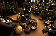 Hamar women serve millet porridge at a feast held after a bull jump, in South Omo, Ethiopia. The bull jump is a ritual at which a man runs over a row of bullocks in order to become eligible for marriage. The 40,000-strong, cattle-herding Hamar are among the largest of the 20 or so ethnic groups which inhabit the culturally diverse South Omo region in south-west Ethiopia.