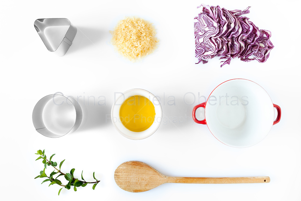 Composition of ingredients and kitchen utensils used for the preparation of red cabbage risotto. Above view over white background, natural light.