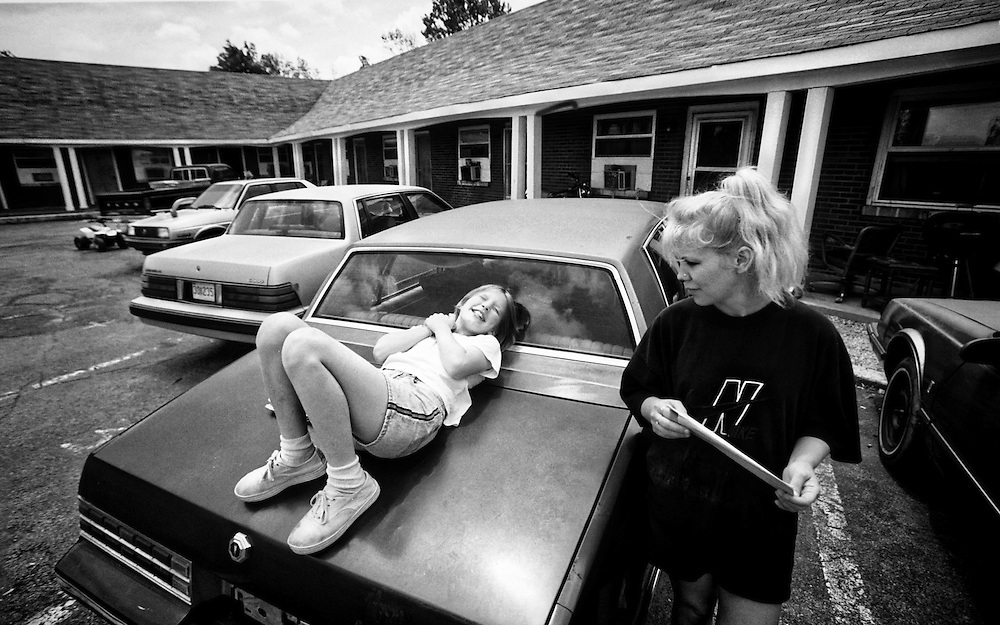A nervous Cora McNeil, right, waits for word why her oldest son, Ryan, 8, didn't get off the bus when the rest of the kids got home from school. Her oldest daughter, Shannon, 11, didn't seem worried as she rests on top of a neighbor's car at the Town and Country Motel where the family lives. It turned out Ryan had fell asleep on the bus and missed his stop. (Mike Fender Photo) w/ story