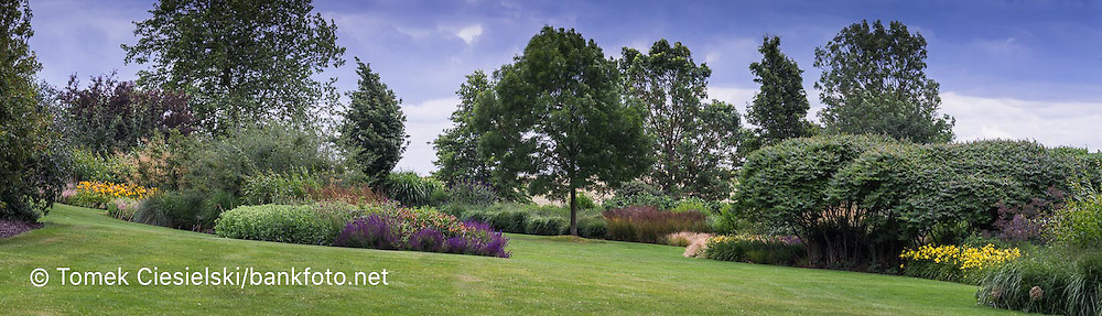 Panoramic view for a long flowerbeds with ornamental grasses summer perennials and deciduous trees.