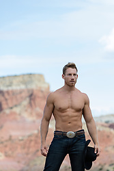 Muscular shirtless cowboy outdoors on a mountain range