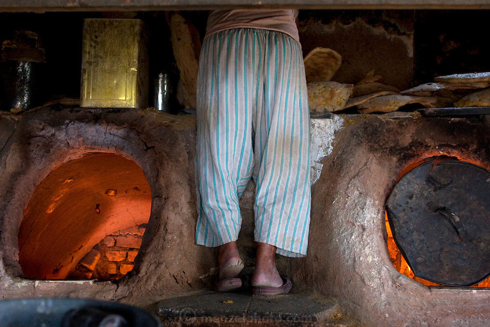 Akbar Zareh reaches above the circular ovens at his bakery in the city of  Yazd, Iran. (From the book What I Eat: Around the World in 80 Diets.) MODEL RELEASED.