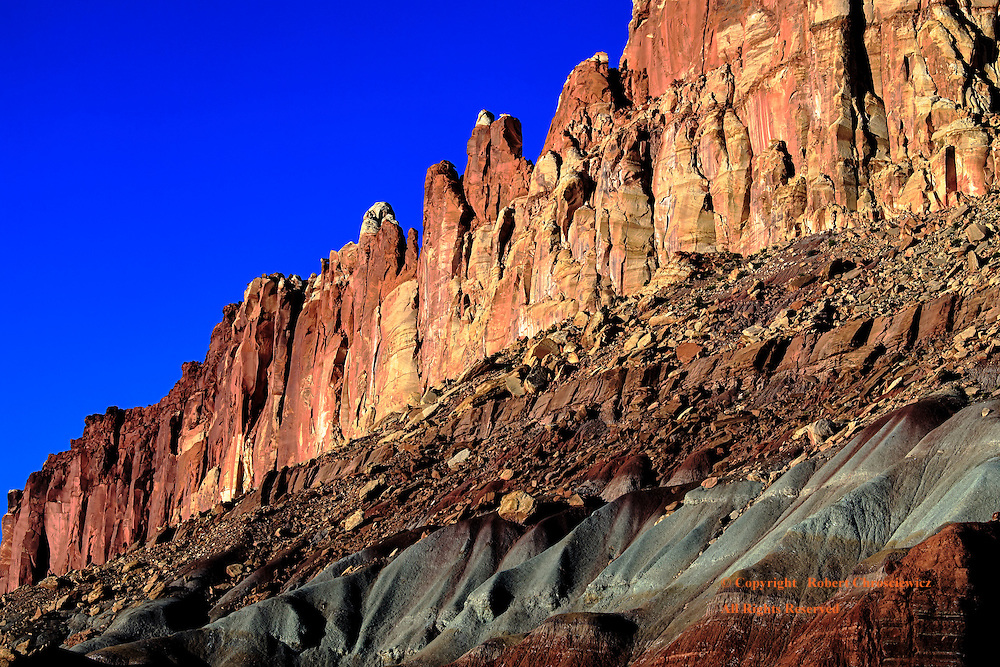 The colourful, weathered and striated rock face stands in a vertical pose against the clear blue sky at sunset, the &quot;Scenic Drive&quot;, Capital Reef National Park, Utah USA.<br /> <br /> .