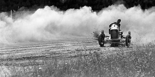 "LOOSE! The American oval track word for ""oversteer"" is beautifully illusrated by this driver aboard his dirt car at Altamont Fairgrounds near Albany, NY. Photo taken 1938 with medium-format view camera by Ozzie Lyons."