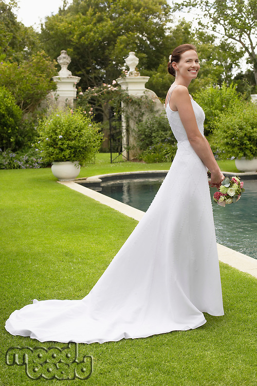 Mid adult bride at poolside holding bouquet side view