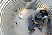 Watershed Management Group intern Omar Ore-Giron prepares the inside of the cistern for seal coating.