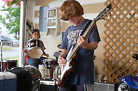 Two boys (10-12) playing drums and guitar in garage