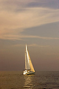 A Sailboat sails in the sunset on the Saginaw Bay