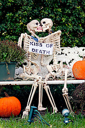 30 October 2015. New Orleans, Louisiana.<br /> The Skeleton Krewe mansion on St Charles Avenue at the corner of State Street draws crowds with its satirically spooky Halloween decorations. Two skeletons embrace in the 'Kiss of Death.'<br /> Photo©; Charlie Varley/varleypix.com