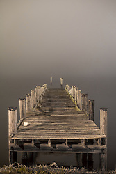 Old tattered and broken pier leading out into the fog