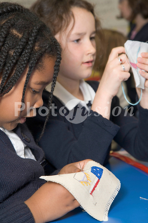 Primary school pupils learning to sew during a needlework lesson at school,