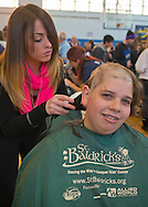 SKLYER NASH, 14, a high school freshman from Merrick, has his head shaved at the St. Baldrick's fund raising event at Calhoun High School. The Long Island school exceeded its goal of raising $50,000 for childhood cancer research. Plus, many ponytails cut off will be donated to Locks of Love foundation, which collects hair donations to make wigs for children who lost their hair due to medical reasons.S