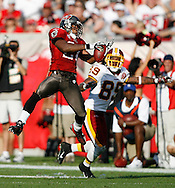 CAPTION: (Tampa 11/25/07) (photo#4) Ronde Barber leaps up for a fourth quarter interception in front of Washington's (89) Santana Moss. It was his 32nd career interception, passing Donnie Abraham to become the all-time Buccaneer career interception leader..BRENDAN FITTERER | Times.SUMMARY: Tampa Bay Buccaneers vs. Washington .Redskins Sunday (11/25/07) at Raymond James Stadium