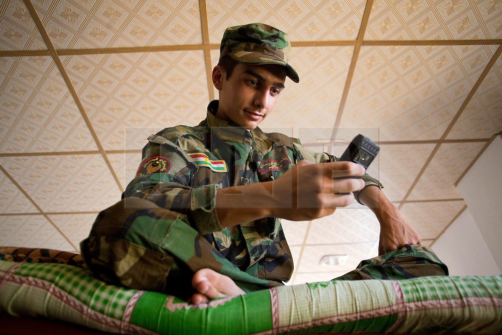 © Licensed to London News Pictures. 29/06/2014. Khanaqin, UK  Khanaqin, Iraq. A young Kurdish peshmerga fighter, who has not completed his military training, uses a mobile phone on his bunk bed at a peshmerga base in Khanaqin, Iraq. Counted by Kurds as part of their homeland, fighting in the town of Jalawla now consists of occasional skirmishes and exchanges of fire between snipers and heavy machine guns on both sides.<br /> The peshmerga, roughly translated as those who fight, is at present engaged in fighting ISIS all along the borders of the relatively safe semi-automatous province of Iraqi-Kurdistan. Though a well organised and experienced fighting force they are currently facing ISIS insurgents armed with superior armament taken from the Iraqi Army after they retreated on several fronts. Photo credit : Matt Cetti-Roberts/LNP