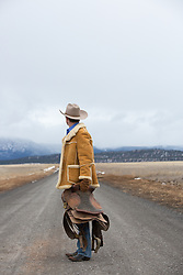 cowboy holding a saddle on a dirt road