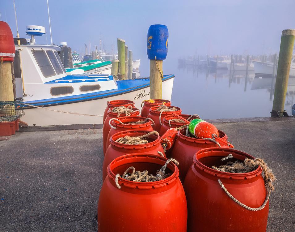 Red barrels & fishing gear on dock, foggy row of boats moored, Galilee, RI