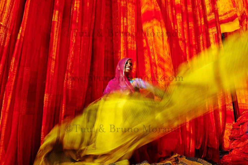 Inde, Rajasthan, Usine de Sari, Sita Devi, 40 ans. Les tissus sechent en plein air. Ramassage des tissus secs par des femmes et des enfants avant le repassage. Les tissus pendent sur des barres de bambou. Les rouleaux de tissus mesurent environ 800 m de long. . // India, Rajasthan, Sari Factory, Sita Devi, 40 old. Textile are dried in the open air. Collecting of dry textile  are folded by women and children. The textiles are hung to dry on bamboo rods. The long bands of textiles are about 800 metre in length.