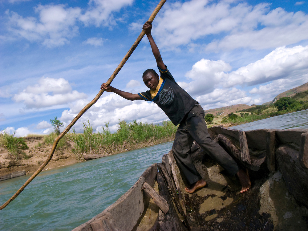 A boy carries passengers across the Artibonite river.
