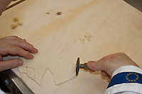 making leaves decorations using a specific tool on wooden counter, two small leaves on coounter, Sardinian bread sculpture, the Pani Pintau