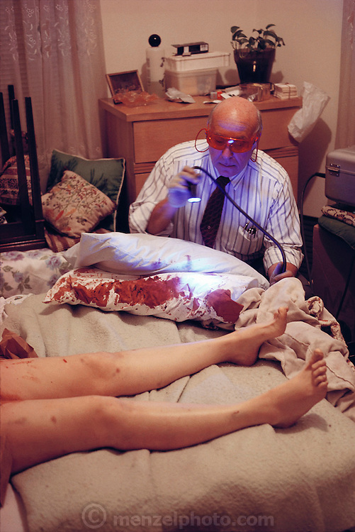 (1992) Forensic scientist at a scene of crime. The scientist here is using a laser to look for possible traces of semen at the scene of a murder. The area is sprayed with a marker, which binds to proteins in the semen. If bound, the marker fluoresces under the light from the laser. This was the scene of the murder of a 49-year-old woman who had been stabbed repeatedly. Traces of semen may be used to provide a DNA fingerprint, possibly linking a suspect to the scene.  Flushing, New York. (Scientist is Detective Roussine, NYPD.) DNA Fingerprinting. MODEL RELEASED.
