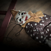 A old clown puppet with a porcelain face lying on the floor.