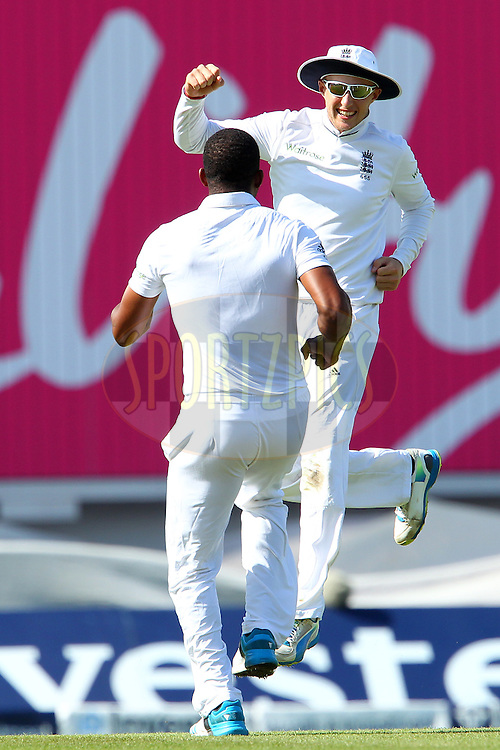 Joe Root of England celebrates the wicket of Virat Kohli of India with Chris Jordan of England during day three of the fifth Investec Test Match between England and India held at The Kia Oval cricket ground in London, England on the 17th August 2014<br /> <br /> Photo by Ron Gaunt / SPORTZPICS/ BCCI