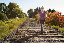 United States, Washington, Kirkland, woman walking on railroad track on site of future Kirkland Corridor rail trail.  MR